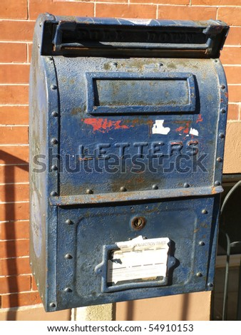 old blue letter box in front of a red brick wall - stock photo