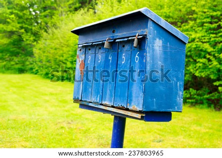 Old blue mailbox on a stake somewhere  in the country - stock photo