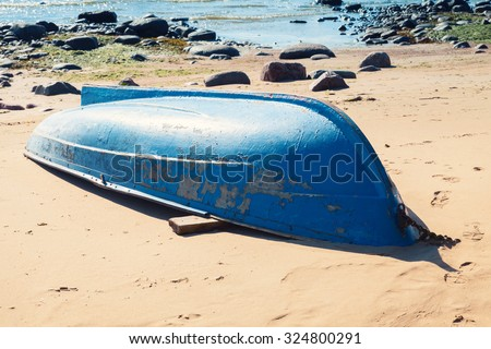 Old blue rowboat lays on sandy beach. Gulf of Finland, Russia - stock photo