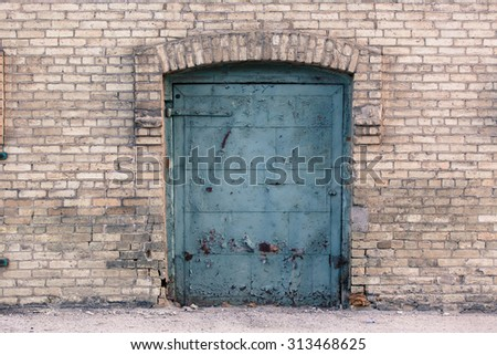 Old blue rusted door in industrial area against light colored brick wall - stock photo
