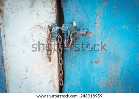 Old blue steel door closed by a chain. - stock photo