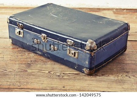 Old blue suitcase on the wooden vintage floor - stock photo