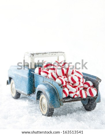 Old blue toy truck carrying striped peppermint candy on white snowy background - stock photo