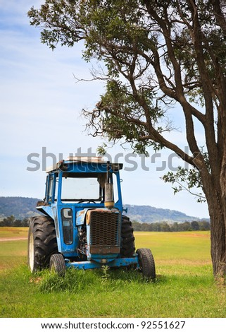 Old blue tractor in field - stock photo
