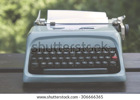 old blue typewriter on a garden wooden table, vintage stock phot - stock photo