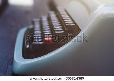 old blue typewriter on a garden wooden table, vintage stock photo - stock photo