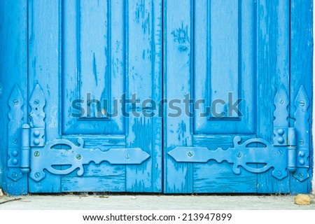 Old blue window shutters with decorative hinges - stock photo