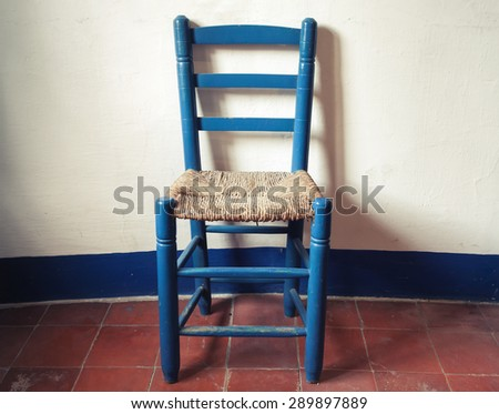 Old blue wooden chair with wicker seat stands in empty interior, white wall and red floor tiling. Vintage style. Photo with toned instagram filter effect - stock photo