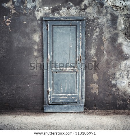 Old blue wooden door in dark concrete wall, empty abstract interior, square background texture - stock photo
