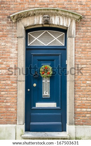 Old blue wooden door on a red brick wall, Bruges, Belgium