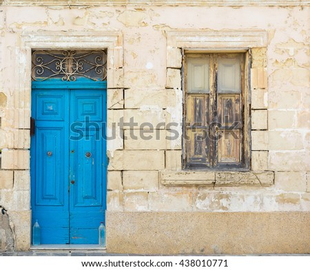 Old blue wooden vintage door and window in ruin, middle age limestone house - Malta, Mdina. Good for 3d models texture. Outdoor.