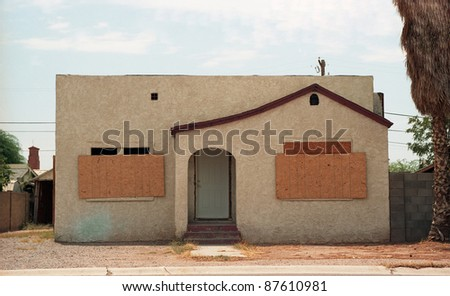 Old boarded up abandoned house - stock photo