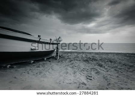 Old boat abandoned at the beach - stock photo