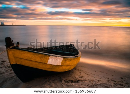 Old boat at beach during sunset