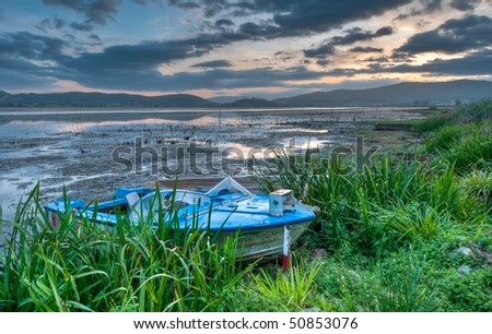 Old boat at lakeside at sunrise - stock photo