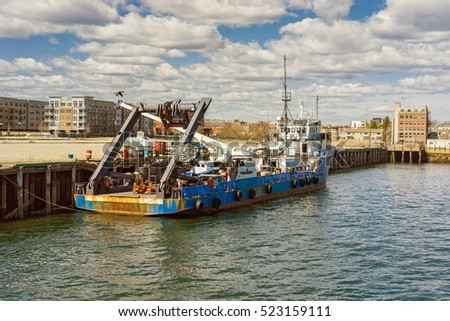 Old boat floating on water in the harbor in Boston, United States of America. The city is located near many water facilities and it is common to travel using water transport such as ferry boats.