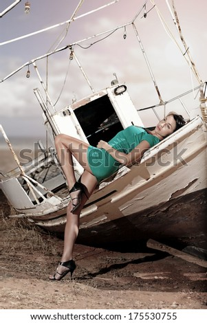 old boat in the land and a sexy girl with green dress posing  - stock photo