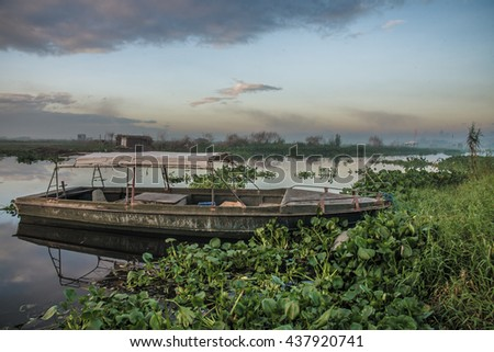 Old boat on the lake. Old boat at a green shore at the lake. Boat on the lake sunset. Old boat on the background of the sky - stock photo