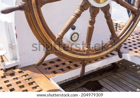 Old boat steering wheel from brass and wood - stock photo