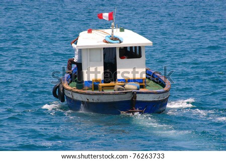 Old boat with cabin is sailing away, visible aft and Peruvian flag - stock photo