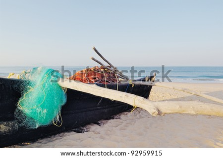Old boat with fishing net on sandy beach. In Goa - stock photo