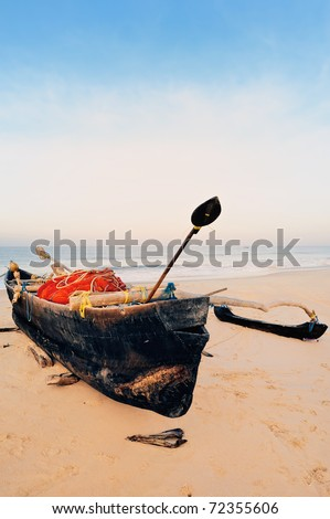Old boat with fishing net on sandy shore. In Goa - stock photo