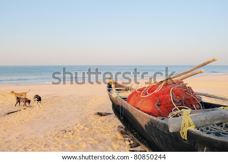 Old boat with red fishing net on sandy shore - stock photo