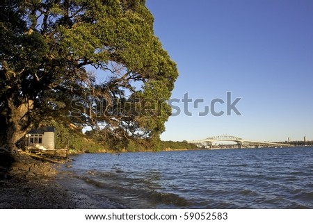Old boathouse and Auckland Harbour Bridge, North Island, New Zealand. - stock photo
