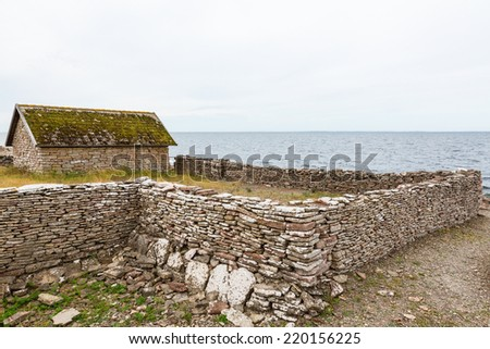 Old boathouse with stone wall on the shore - stock photo
