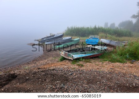 Old boats at the foggy riverbank. Siberia, Enisey, Russia. - stock photo