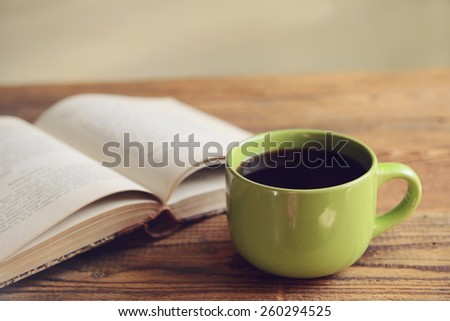 old book and a cup of coffee on a wooden background, toned image - stock photo