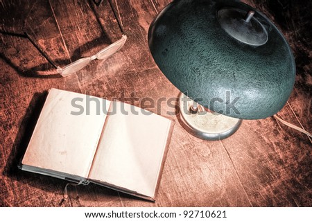 Old book and electric lamp in retro style - stock photo