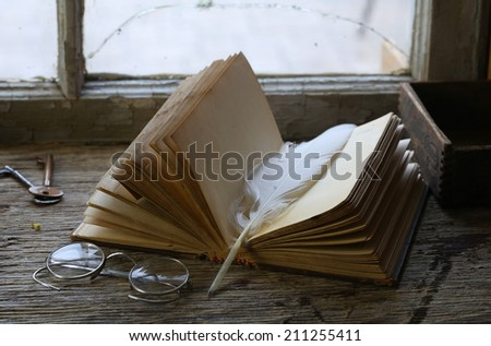 Old book and eyeglasses on shelf by window  - stock photo