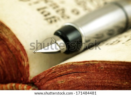 Old book and fountain pen (macro photo) - stock photo