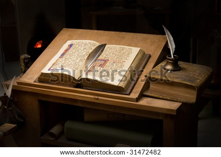 Old book and inkpot in a library table.