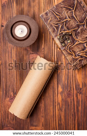 Old book, candle and letter on wooden table - stock photo