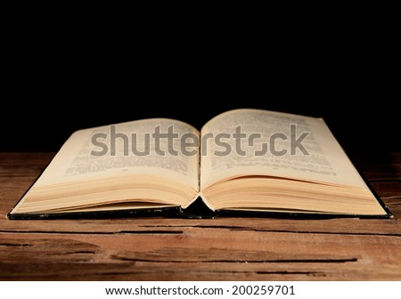 Old book on table on black background - stock photo