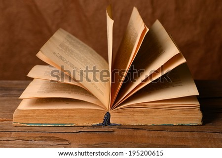 Old book on table on brown background