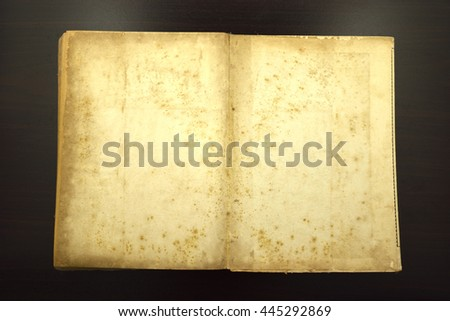 Old Book on the table. reflect light on the wooden floor. - stock photo