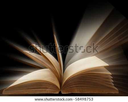 old book open bright light on black background - stock photo
