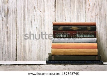 old book shelf blank spines, empty binding stack on wood texture background, knowledge concept - stock photo