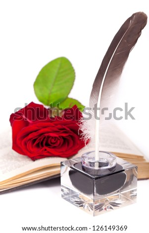 old book with a rose, feather and ink bottle isolated on white background, feather pen and inkwell - stock photo