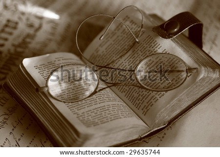 Old book with ancient eyeglasses on document - stock photo