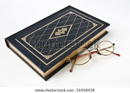 Old book with eye glass - stock photo