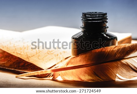 Old book with feather pen and inkpot - stock photo