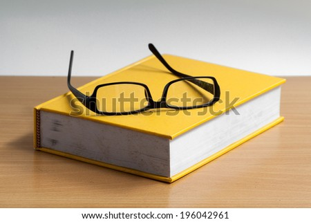 old book with glasses - stock photo