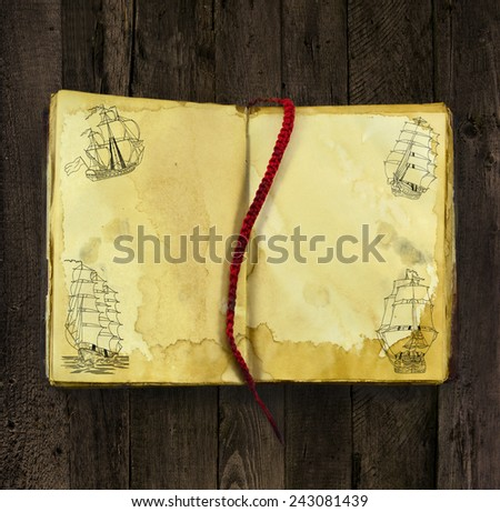 Old book with hand drawn silhouettes of sailing ships on shabby pages on grunge wooden background - stock photo
