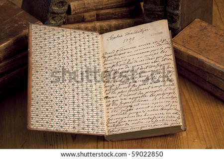 Old book with handwritten text from 1798 lying on a wooden table with books in the background. - stock photo
