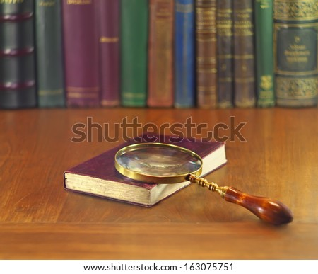 old book with leather cover and vintage magnifying glass - stock photo