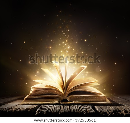 Old Book With Magic Lights On Vintage Table  - stock photo
